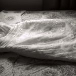 b&w photo of traditional wedding dress lying on a bed